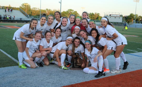 Plymouth's soccer team poses with its first regional championship trophy.