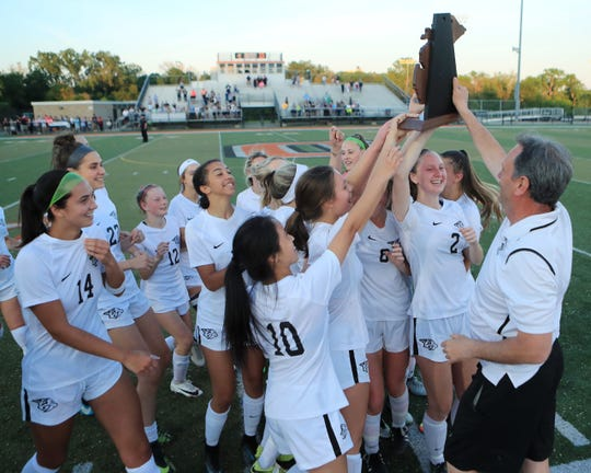 Plymouth coach Jeff Neschich holds up the Wildcats' Division 1 regional soccer trophy to the delight of his team.