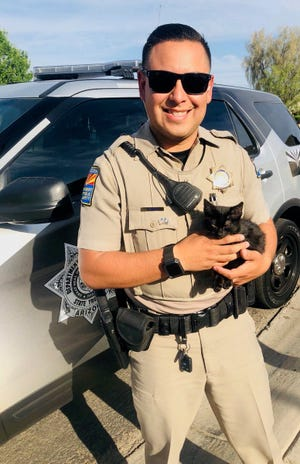 Trooper Montes poses with Trooper, a kitten who was thrown from a car that was driving down a highway.
