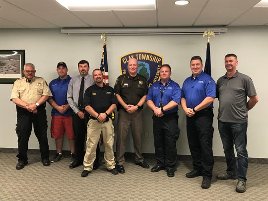St. Clair County Sheriff Tim Donnellon, center, and Lt. Paul Reid, left, stand with Clay Township officers. Seven were deputized to help enforce wake rules on the water.