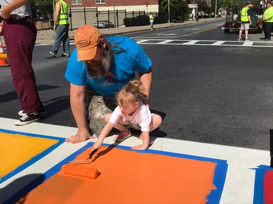 "Michael Kurtz, 41, of the Town of Poughkeepsie assists his daughter, Aurora, 3, as she paints a crosswalk on Main Street in the City of Poughkeepsie Saturday. The crosswalk was painted as part of ""Poughkeepsie Pride Weekend."""