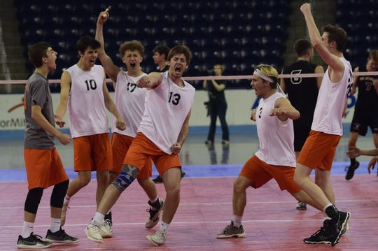 York Suburban's Nate Bowman punches the air and his teammates surround him after the Trojans pulled off a comeback to win Game 4 of the PIAA Class 2A boys' volleyball championship Saturday, June 8, 2019 in State College.
