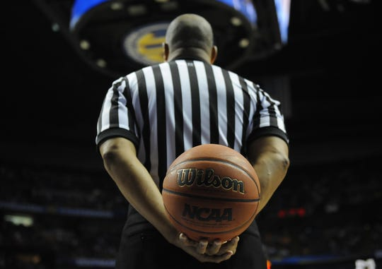 A referee holds the basketball in a timeout during an NCAA basketball game