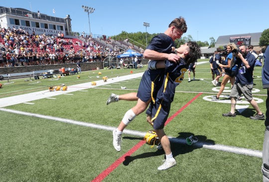 Victor's Richie Pierpont lifts teammate Camden Hay off the ground as the team celebrates its state Class B championship.