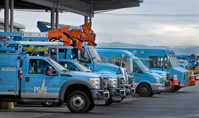 In this Jan. 14, 2019, file photo, Pacific Gas & Electric vehicles are parked at the PG&E Oakland Service Center in Oakland, Calif. The year's first fire danger warning in Northern California is putting Pacific Gas & Electric on alert.