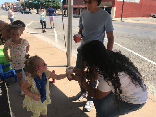 Harley Ratliff gives a customer some lemonade at her stand in front of FOX West Texas, 5 S. Chadbourne St., on Saturday, June 8, 2019.