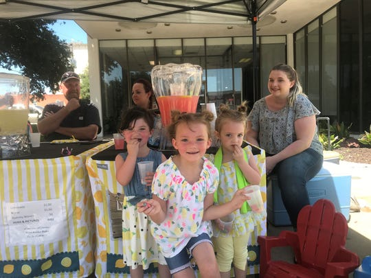 Harley Ratliff poses with her sister Emily and her friend Lily at her lemonade stand at 5 S. Chadbourne St. Saturday, June 8, 2019.