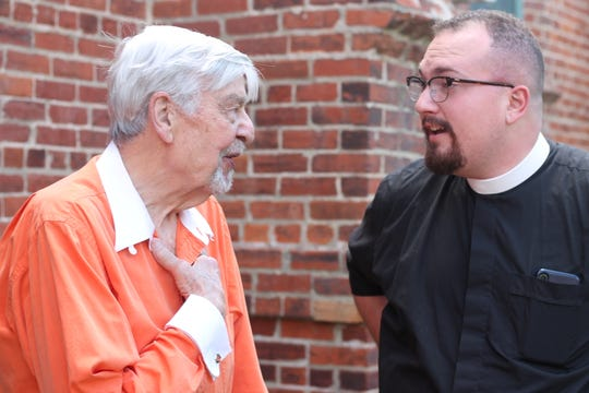 Seminarian J. Garrett Boyte speaks with Shreveport resident at a Wear Orange event at Holy Cross church downtown