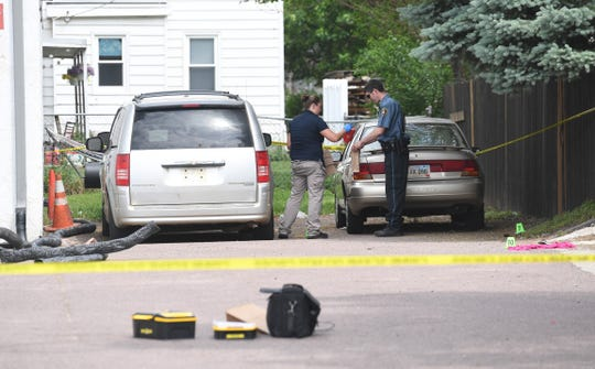 Police check evidence while investigating a shooting on Cliff Ave. on Saturday, June 8, in Sioux Falls.