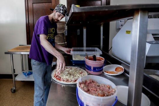 William Rodgers, 31, of Plover, prepares a pizza for an order on Friday, June 7, 2019, at Mickey T's Club 10 in Stevens Point, Wis.