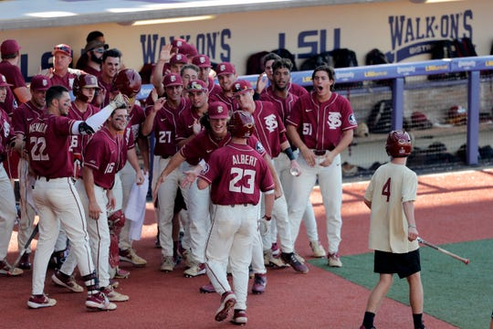 Florida State's Albert Reese is greeted at the dugout ofter his solo homer, his second home run of the day against LSU, in the ninth inning of Game 1 of the NCAA college baseball super regional tournament in Baton Rouge, La., Saturday, June 8, 2019. Florida State won 6-4. (AP Photo/Gerald Herbert)