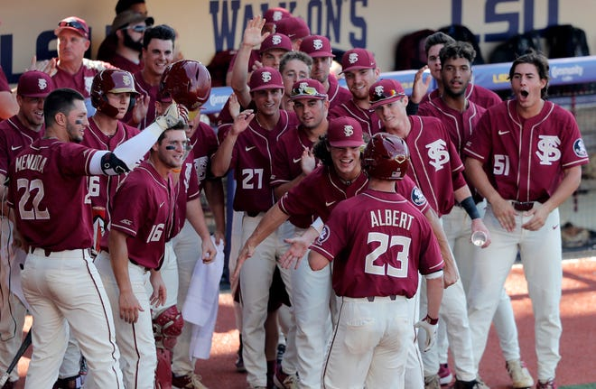 Florida State's Reese Albert (23) is greeted at the dugout after his solo home run, his second home run of the day, against LSU in the ninth inning of Game 1 of the NCAA college baseball super regional tournament in Baton Rouge, La., Saturday, June 8, 2019. (AP Photo/Gerald Herbert)