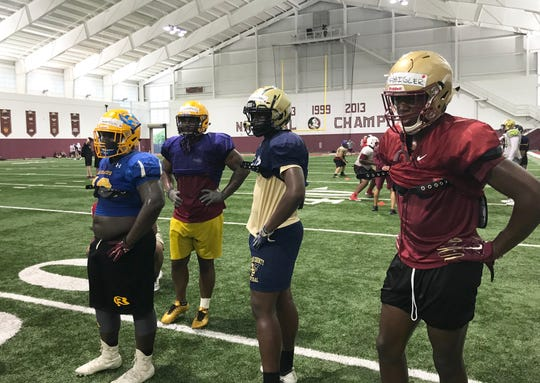 From left to right: Jonathyn Donaldson (Rickards High School), Daylon Lumpkin (Columbia High School), Jaylen Bowden (Thomas County Central High School) and Marcus Haigler (Florida High School) listen to their coaches at the Willie Taggart Big Man Camp.