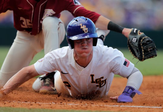 LSU's Daniel Cabrera, bottom, avoids a tag by Florida State first baseman Carter Smith (35) in the fifth round of Game 1 of the NCAA Baseball Super Regional Tournament in Baton Rouge, La., Saturday, June 8, 2019. (AP Photo / Gerald Herbert)