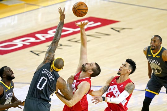 Raptors center Marc Gasol (33) goes for a rebound against the Warriors' DeMarcus Cousins (0) during the first quarter of Game 4 of the NBA Finals. Gasol, who was acquired in a trade from the Grizzlies this season, has helped Toronto to within one win of its first championship.