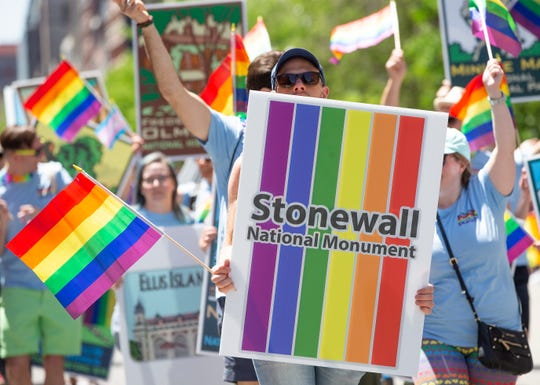 A parade participant holds a placard to commemorate the Stonewall riot as he takes part in the 49th Boston Pride Parade honoring equal rights for all persons and the 50th anniversary of the Stonewall riots, in Boston, Mass. on June 8, 2019. Organizers stated in this year's guide, 'While it is important to commemorate the golden anniversary of Stonewall, we did not want to lose sight of the significant activism that occurred both before and after the legendary riots.'