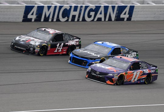 Denny Hamlin (11), Ryan Newman (31), and Clint Bowyer (14) race three-wide during the 2018 FireKeepers Casino 400 at Michigan International Speedway.