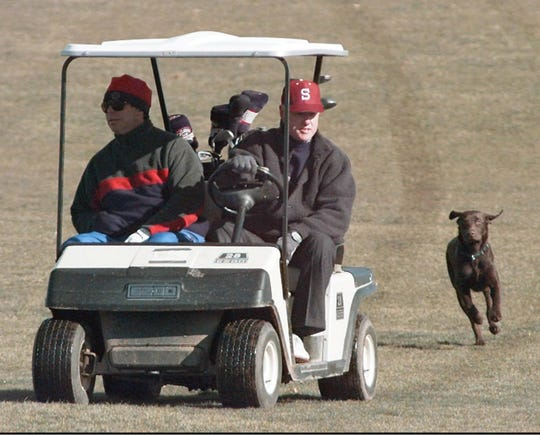 US President Bill Clinton (R) rides his golf cart down the 9th fairway with Tony Rodham, the brother of Hillary , as the Presidents dog Buddy chases behind during a round at the Maple Run Golf Club in Thurmont, Maryland. The President is spending the weekend at Camp David with his daughter Chelsea while his wife is traveling.