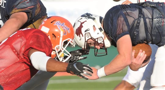 Blue Team quarterback Tommy Bowden of Brownwood, right, crashes into the Red Team's Daylon Green of San Angelo Central. The Blue Team won the Myrle Greathouse All-Star Classic 60-13 June 8 at Shotwell Stadium.