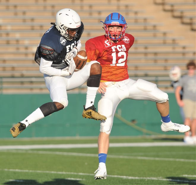 The Blue Team's Jeremiah Cooley of Big Spring tries to complete the catch on a long pass from Tommy Bowden while the Red's Cody Lynch of Gorman looks on. Cooley made the catch, and the Blue Team won the Myrle Greathouse All-Star Classic 60-13 on June 8 at Shotwell Stadium.