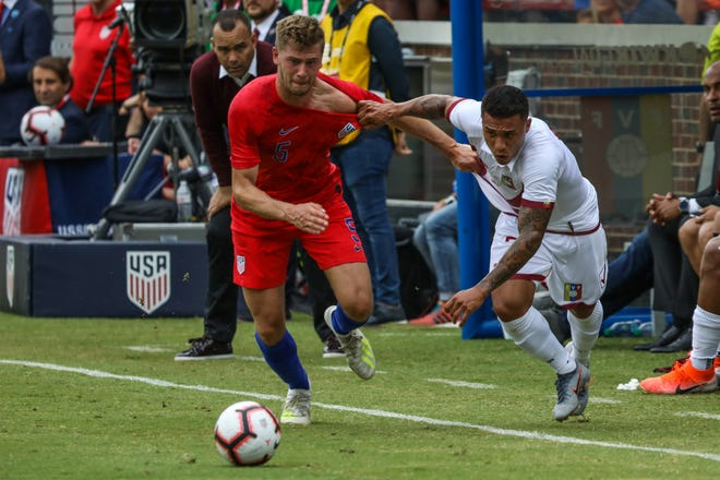 Venezuela's Darwin Machis and USA's Walker Zimmerman fight to get to the ball and keep it in bounds during the USA vs. Venezuela match at Nippert Stadium on Sunday June 9. 2019. Venezuela won the match with a final score of 3-0.