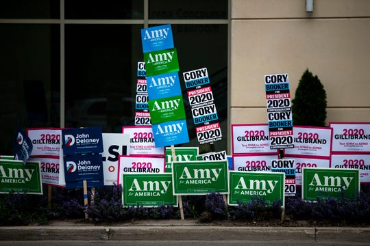 Signs showing support for several of the candidates currently running for president line the street outside of the Iowa Democratic Party's hall of fame event on Sunday, June 9, 2019, in Cedar Rapids.