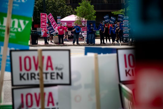 Groups of supporters for several of the candidates currently running for president line the street outside of the Iowa Democratic Party's hall of fame event on Sunday, June 9, 2019, in Cedar Rapids.
