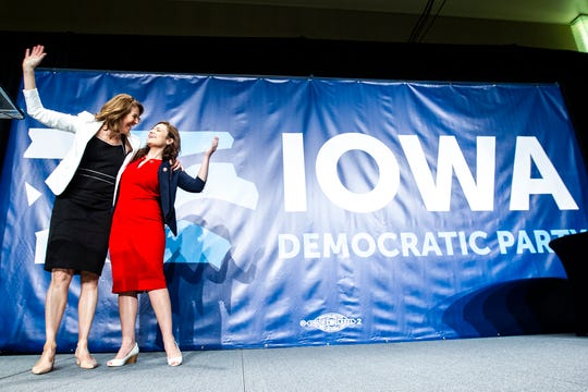 U.S. Reps. Cindy Axne, left, and Abby Finkenauer of Iowa wave while taking the stage during the Iowa Democratic Party Hall of Fame dinner, Sunday, June 9, 2019, at the DoubleTree by Hilton in Cedar Rapids, Iowa.
