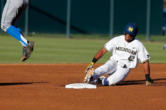 Michigan's Jordan Nwogu slides safely into second base during the first inning of an NCAA college baseball tournament super regional game against UCLA in Los Angeles, Saturday, June 8, 2019.