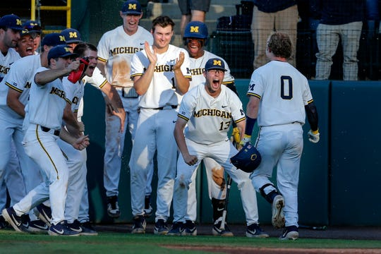 Michigan's Joe Donovan (0) is greeted by teammates after hitting a home run against UCLA during the second inning of an NCAA college baseball tournament super regional game in Los Angeles, Saturday, June 8, 2019.