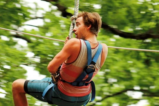 A climber flies down a zipline at TreeRunner Adventure Park.