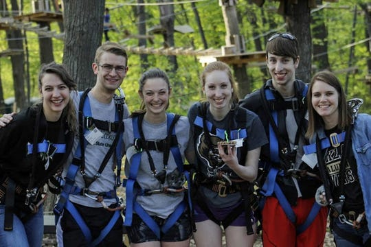 A group poses in harnesses at TreeRunner Adventure Park.