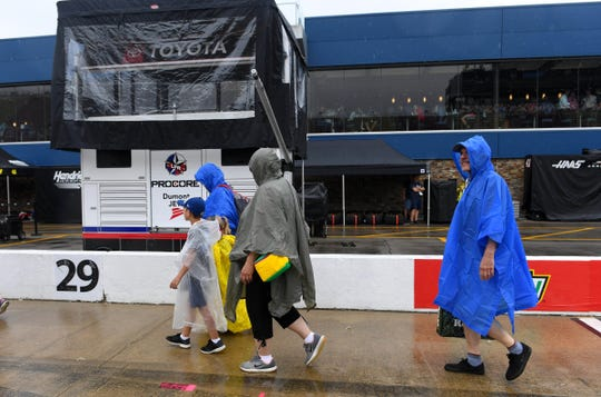NASCAR fans leave pit row after heavy rain cancels the pre-race activities before the FireKeepers Casino 400 at Michigan International Speedway, Sunday.