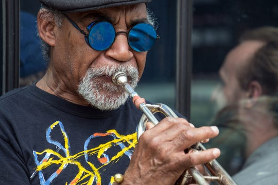 Musician Earle Davis plays his trumpet outside Avalon Bakery and Cafe in Detroit's Midtown in April. Davis uses a bicycle to get around Detroit year round and uses bike lanes when available.