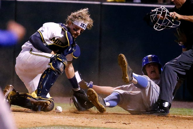 UCLA's Jake Moberg slides safe into home against Michigan catcher Joe Donovan during the 12th inning.