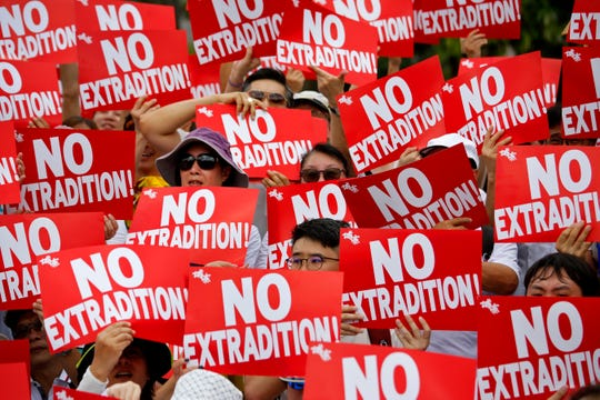 Protesters hold placards as they protest the extradition law in Hong Kong, Sunday.