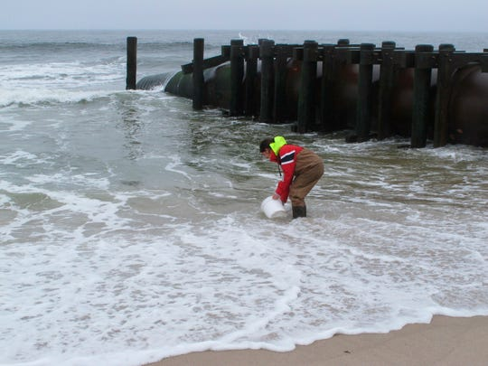 Skye Post, who will be a junior at Monmouth University this fall, takes an ocean water sample near a storm drain outfall pipe on the beach in Long Branch, N.J., on May 30.