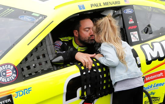 Paul Menard receives a kiss from his daughter Remi before the NASCAR Cup series auto race at Michigan International Speedway on Sunday.