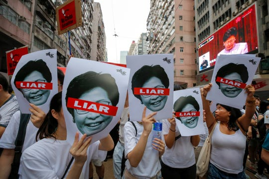 Protesters hold pictures of Hong Kong Chief Executive Carrie Lam as protesters march along a downtown street against the proposed amendments to an extradition law in Hong Kong Sunday, June 9, 2019. A sea of protesters is marching through central Hong Kong in a major demonstration against government-sponsored legislation that would allow people to be extradited to mainland China to face charges. (AP Photo/Kin Cheung)