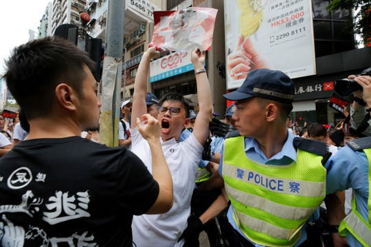 A protester shouts next to policemen as protesters march in a rally against the proposed amendments to extradition law in Hong Kong, Sunday.