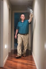 Paranormal investigator and Reiki Master Joe Weigant smudges the hallway during a house cleaning on Evansville's Northside Sunday, May 26, 2019.