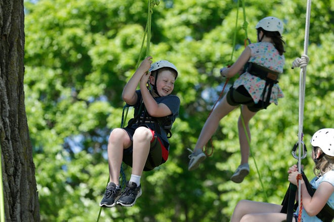 Kids rappel from a tree at Walleye Weekend on June 8, 2019, at Lakeside Park in Fond du Lac.