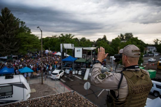 A Fort Collins Police Services SWAT team member waves at a festival goer while looking over the crowd on a public venue overwatch mission during the second day of Taste of Fort Collins on Saturday, June 8, 2019, in Fort Collins, Colo.