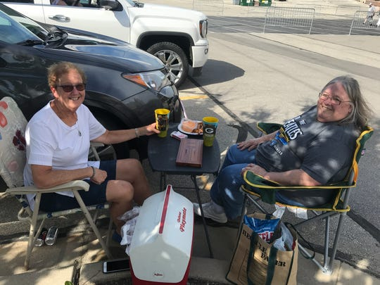 Cris Clay (left) and Marilyn Zirbel set up in the Lambeau Field parking lot as soon as the lots opened at 4 p.m.