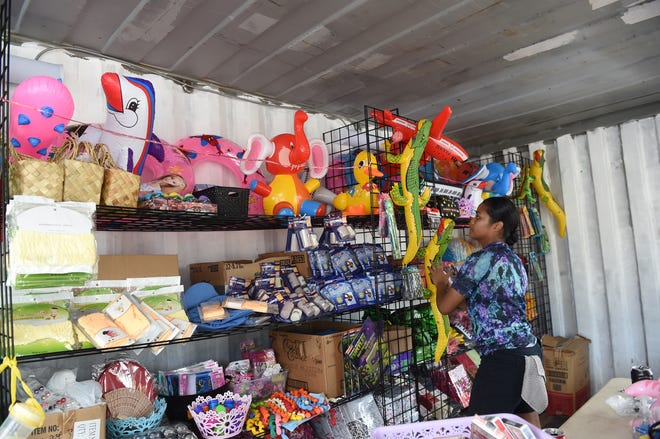 "Volunteer Cassandra Towai organizes prizes at the ""Spin-to-win"" game booth in preparation for the opening of the 75th Liberation Carnival at Paseo de Susana Park in Hagåtña in this June 9, 2019, file photo. An audit of the 75th Guam Island Fair and Liberation Day Carnival found it didn't comply with Guam procurement rules and regulations."
