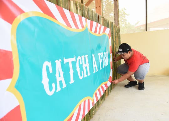 """Alan Guzman, 11, adjusts a banner for his auntie's """"Catch a fish"""" game booth in preparation for the opening of the 75th Liberation Carnival at Paseo de Susana Park in Hågatña, June 9, 2019."""