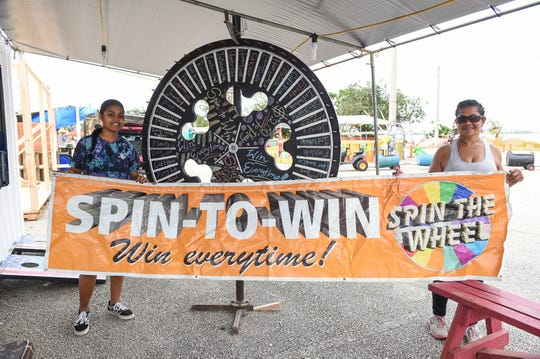 "Cassandra Towai, left, and Mary Solang hold up their ""Spin-to win"" game booth banner at Paseo de Susana Park in Hagåtña, June 9, 2019."