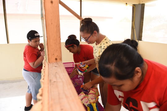 """Volunteers organize prizes for their """"Catch a fish"""" game booth in preparation for the opening of the 75th Liberation Carnival at Paseo de Susana Park in Hagåtña, June 9, 2019."""