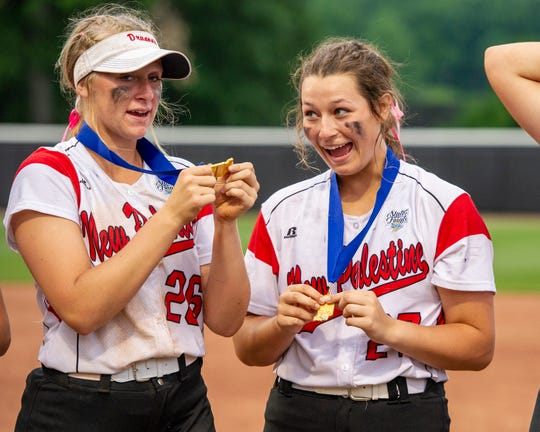 New Palestine High School senior Tatum Biddle (26) and sophomore Sam Booe (27) celebrate their win with their medals. New Palestine High School took on Yorktown High School, Saturday, June 8, 2019, in the 35th Annual IHSAA Class 3A Softball State Finals at Bittinger Stadium on the campus of Purdue University in West Lafayette, Ind. New Palestine won the game 10-0.