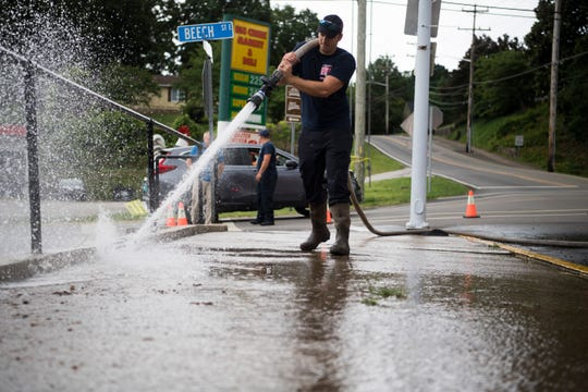 Mason Capps of the LaFollette Fire Department cleans mud off Tennessee Avenue in front of the police department June 9, 2019.